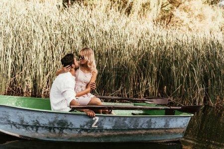 Photo pour Un jeune couple embrassant et embrassant un bateau sur la rivière près d'un bosquet de carex - image libre de droit