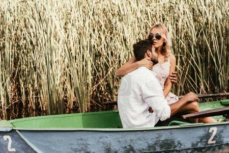 Photo pour Jolie jeune femme embrassant son copain en bateau sur un lac près d'un bosquet de carex - image libre de droit