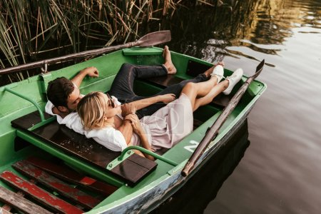 Photo pour Happy young couple relaxing in boat on lake near thicket of sedge - image libre de droit