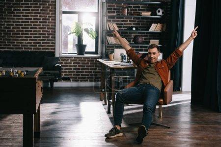 Photo pour Jeune homme d'affaires heureux, assis en fauteuil et faisant un geste de vainqueur - image libre de droit