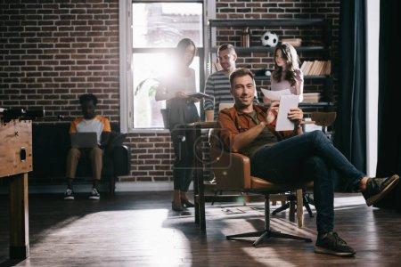 Photo pour Jeune homme d'affaires souriant assis en fauteuil avec une tablette numérique près de collègues multiculturels - image libre de droit