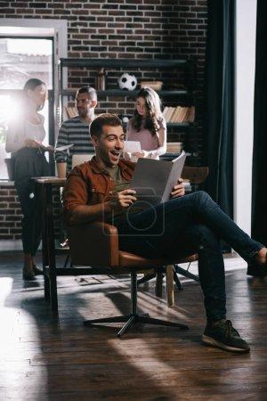 Photo pour Un homme d'affaires gai assis en fauteuil et lisant un document près de ses jeunes collègues - image libre de droit