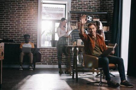Photo pour Un homme d'affaires gai assis en fauteuil et faisant la main à la caméra près de jeunes collègues multiculturels - image libre de droit