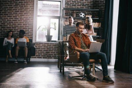 Photo pour Un homme d'affaires souriant assis dans un fauteuil et utilisant un ordinateur portable près de jeunes collègues multiculturels - image libre de droit