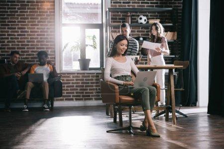 Photo pour Séduisante femme d'affaires assise dans un fauteuil et utilisant un ordinateur portable près de jeunes collègues multiculturels - image libre de droit