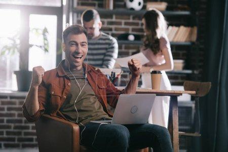 Photo pour Homme d'affaires joyeux dans les écouteurs assis dans le fauteuil, en utilisant un ordinateur portable et montrant geste gagnant près de jeunes collègues - image libre de droit