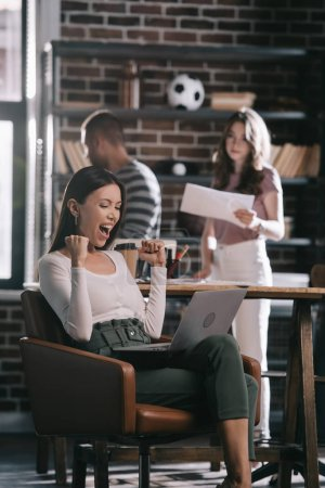 young businesswoman sitting in armchair with laptop and showing winner gesture near colleagues