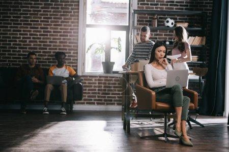 Photo pour Femme d'affaires réfléchie assise dans un fauteuil et utilisant un ordinateur portable près de jeunes collègues multiculturels - image libre de droit