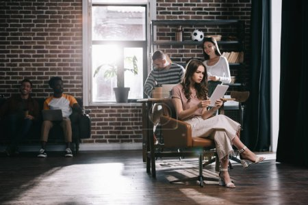 Photo pour Femme d'affaires concentrée assise dans un fauteuil et utilisant une tablette numérique près de jeunes collègues multiculturels - image libre de droit