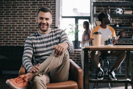 Photo pour Homme d'affaires joyeux souriant à la caméra assis dans un fauteuil près de jeunes collègues multiculturels - image libre de droit