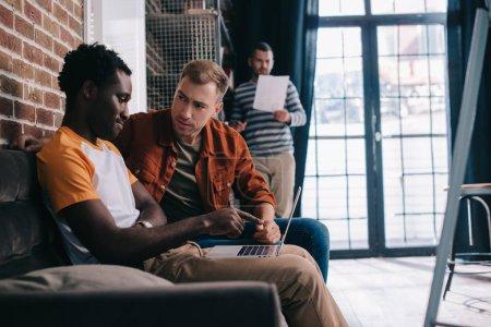 Photo pour Jeune homme d'affaires afro-américain pointant du doigt un ordinateur portable assis sur un canapé près d'un collègue - image libre de droit