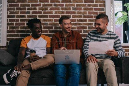 Photo pour Joyeux hommes d'affaires multiculturels assis sur le canapé près du mur de briques et de discuter des idées d'affaires - image libre de droit