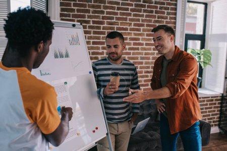 Photo pour Jeunes gens d'affaires multiculturels se tenant près du tableau à feuilles mobiles avec infographie et discutant d'idées d'affaires - image libre de droit