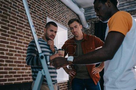 Photo pour Gens d'affaires multiculturels réfléchis se tenant près du tableau à feuilles mobiles avec infographie et discutant d'idées d'affaires - image libre de droit