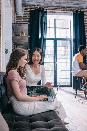 junge Geschäftsfrau benutzt Laptop, während sie auf Sofa neben lächelndem Kollegen sitzt