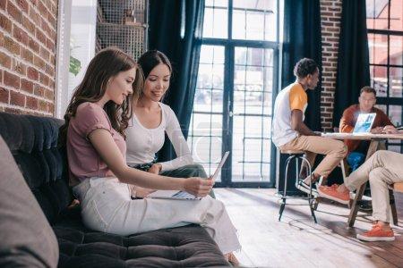 молодые деловые женщины, смотрящие на ноутбук, сидя на диване рядом с коллегами по мультикультурности