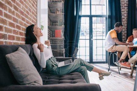 Photo pour Femme d'affaires excitée montrant geste gagnant tout en étant assis sur le canapé près de collègues multiculturels - image libre de droit