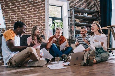 Photo pour De jeunes entrepreneurs multiculturels heureux, assis par terre et faisant des gestes gagnants - image libre de droit