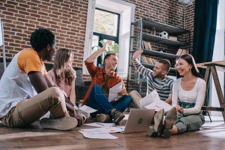 Photo pour Des hommes d'affaires heureux donnant cinq étoiles alors qu'ils étaient assis par terre près de jeunes collègues multiculturels - image libre de droit