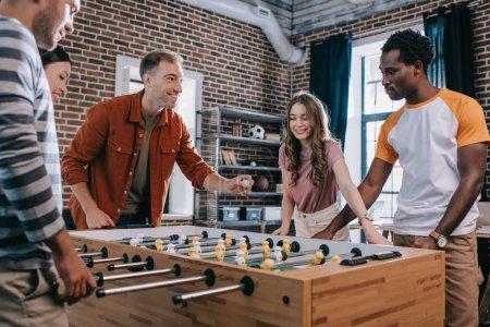 Photo pour Des gens d'affaires multiculturels et gentils jouent au soccer de table au bureau - image libre de droit