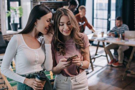 Photo pour Attrayant, souriant femme d'affaires en utilisant smartphone près collègue gai tenant du café pour aller - image libre de droit