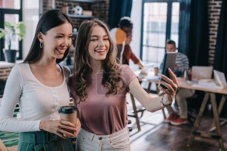Photo pour Jeune femme d'affaires gaie prenant selfie sur smartphone avec collègue gai tenant café pour aller - image libre de droit