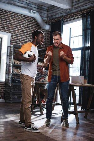 Photo pour Homme d'affaires inquiet gesticulant tout en parlant à un collègue afro-américain tenant un café pour aller - image libre de droit