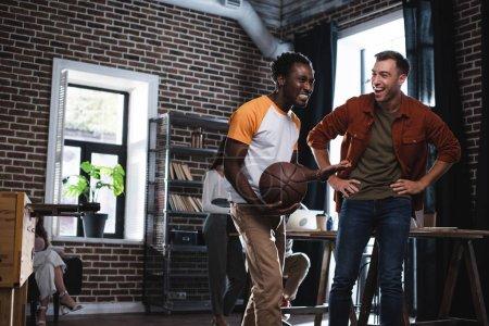 веселый африканский американский бизнесмен, держащий баскетбол, разговаривая с коллегой, стоящим с руками на бедре