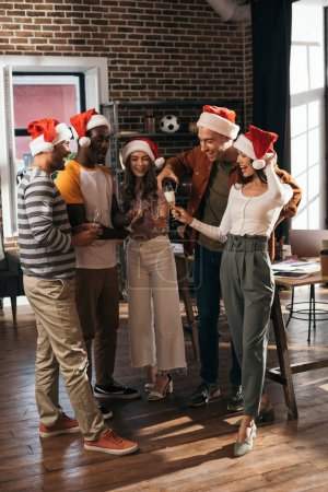 happy multicultural businesspeople in santa hats clinking champagne glasses in office