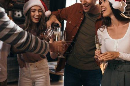 Photo pour Crochet vue d'un homme d'affaires versant du champagne dans des verres de collègues heureux en santa chapeaux - image libre de droit