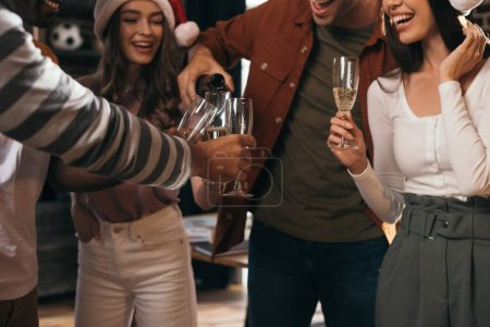 partial view of businessman pouring champagne in glasses of happy colleagues in santa hats
