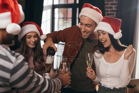 cheerful businessman pouring champagne in glasses of happy colleagues in santa hats
