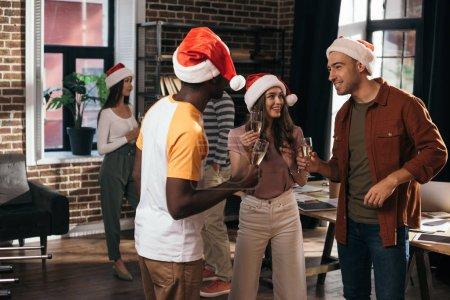 Photo pour Des hommes d'affaires multiculturels et heureux en santa des chapeaux parlant en tenant des verres de champagne au pouvoir - image libre de droit
