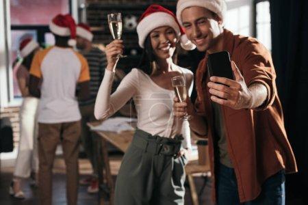 Photo pour Focalisation sélective d'un homme et d'une femme d'affaires gai (e) s dans des chapeaux de santa prendre selfie sur smartphone tout en tenant des lunettes de champagne - image libre de droit