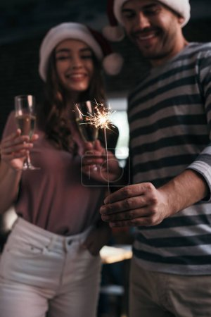 Photo for Selective focus of businessman and businesswoman in santa hats looking at sparkler while holding champagne glasses - Royalty Free Image