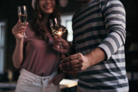 Photo pour Crochet vue d'un homme d'affaires et d'une femme d'affaires portant des chapeaux de santa regardant un étincelant tenant des lunettes de champagne - image libre de droit