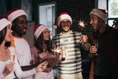 happy, young businesspeople in santa hats holding sparklers and champagne glasses