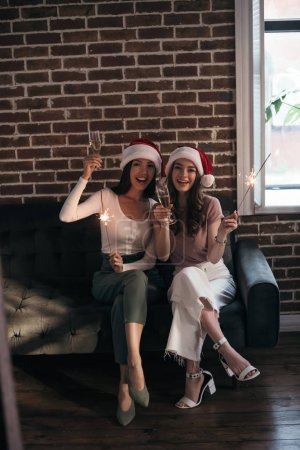 Photo for Two young, happy businesswoman in santa hats smiling at camera while sitting on sofa with sparklers and champagne glasses - Royalty Free Image