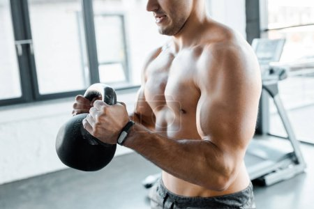 Photo for Cropped view of shirtless sportsman working out with weight in sports center - Royalty Free Image