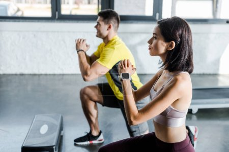 Photo for Side view of handsome sportsman and sportswoman doing lunges in sports center - Royalty Free Image