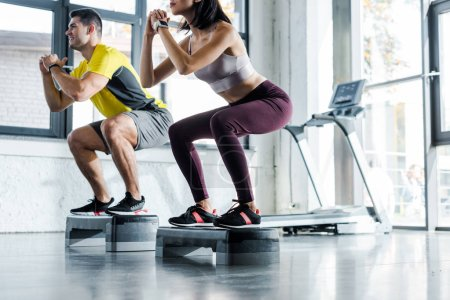 Photo for Cropped view of sportsman and sportswoman doing squat on step platforms in sports center - Royalty Free Image