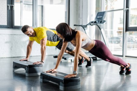 Photo for Handsome sportsman and sportswoman doing plank on step platforms in sports center - Royalty Free Image