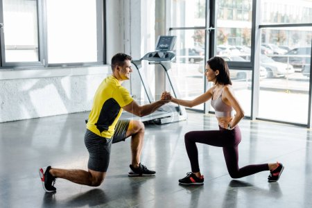 Photo for Side view of sportsman and sportswoman doing lunges together in sports center - Royalty Free Image