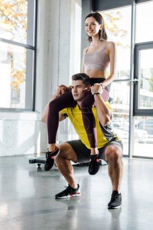 Photo pour Sportsman squatting and holding sportswoman on shoulders in sports center - image libre de droit