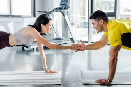 Photo for Smiling sportsman and sportswoman doing plank and clapping on fitness mats in sports center - Royalty Free Image