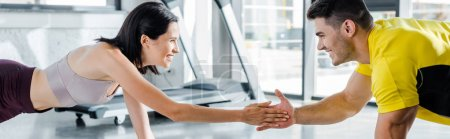 Photo for Panoramic shot of smiling sportsman and sportswoman doing plank and clapping in sports center - Royalty Free Image