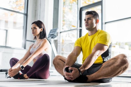 Photo for Sportsman and sportswoman stretching on fitness mats in sports center - Royalty Free Image