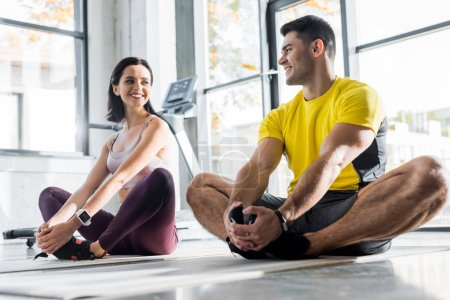 Photo for Smiling sportsman and sportswoman stretching on fitness mats in sports center - Royalty Free Image