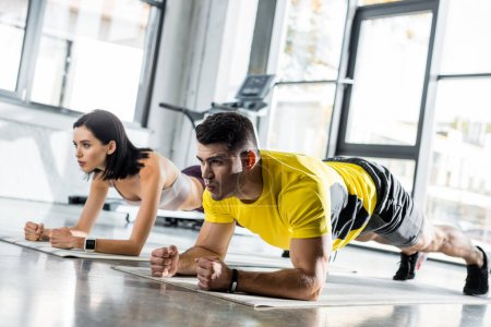 Photo pour Sportsman and sportswoman doing plank on fitness mats in sports center - image libre de droit