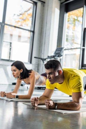 Photo pour Sportsman and sportswoman doing plank on fitness mats in sports center - image libre de droit